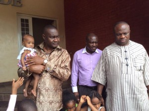 Sen. Magnus Abe accompanied by Hon. Maurice Pronen and Hon. Godwin Bazari, carrying a baby shortly on arrival at the Abuja Children's Home to celebrate his 49th birthday with the Children.